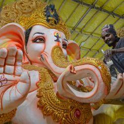 Un trabajador limpia un ídolo del dios hindú con cabeza de elefante Ganesha, en un taller antes del festival Ganesh Chaturthi, en las afueras de Hyderabad. | Foto:NOAH SEELAM / AFP