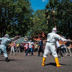 El personal de salud que usa equipo de protección personal (EPP) realiza ejercicios matutinos con pacientes que sufren síntomas leves del coronavirus COVID-19 en un hospital de emergencia en Surabaya. | Foto:Juni Kriswanto / AFP