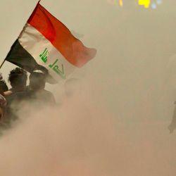 Los manifestantes de raqi se reúnen en medio del humo después de que los servicios de bomberos extinguieran el fuego en los neumáticos durante una protesta cerca de la residencia del gobernador en la ciudad sureña de Basora, para oponerse a los asesinatos y exigir la renuncia de los principales funcionarios de seguridad en la gobernación del sur de Irak. | Foto:Hussein Faleh / AFP
