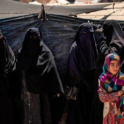 Una niña se encuentra en una fila de mujeres en el campamento de al-Hol dirigido por los kurdos en la gobernación de al-Hasakeh en el noreste de Siria, donde se encuentran detenidas las familias de los combatientes extranjeros del Estado Islámico. | Foto:DELIL SOULEMAN / AFP)