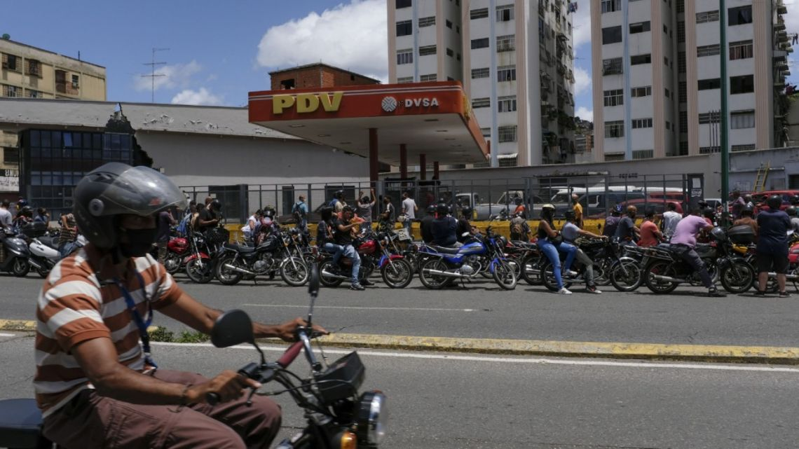 Motorcyclists wearing protective masks wait in line for fuel in at a Petroleos de Venezuela SA (PDVSA) gas station in Caracas, Venezuela, on Friday, August 14, 2020.