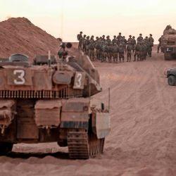 Soldados de infantería israelíes se reúnen junto a tanques y un vehículo blindado de transporte de personal cerca de la frontera israelí con la Franja de Gaza.   Foto:MENAHEM KAHANA / AFP