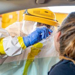 Austria, Ansfelden: un trabajador de la salud con equipo de protección completo toma una muestra de hisopo de una mujer en una estación de prueba de coronavirus (Covid-19) en Ansfelden.   Foto:DPA