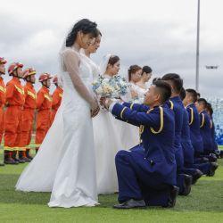 China, Harbin: Diez bomberos ofrecen ramos de rosas a sus novias durante una ceremonia de boda grupal.   Foto:DPA