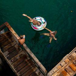 Un niño salta de cabeza al agua a través de un anillo inflable. | Foto:DPA