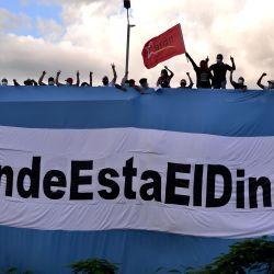 Simpatizantes de los partidos de oposición, Partido Liberal de Honduras (PLH) y Libertad y Refundación (LIBRE), y del Movimiento de los Indignados, se manifiestan en un puente con una bandera hondureña que dice    Foto:ORLANDO SIERRA / AFP