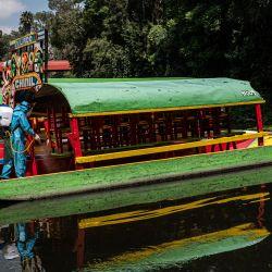 México, Ciudad de México: un trabajador con traje protector desinfecta las coloridas embarcaciones (Trajineras) de Xochimilco, mientras el popular lugar turístico se prepara para reabrir luego de meses de cierre debido a la pandemia de Coronavirus.   Foto:Jacky Muniello / DPA