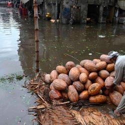 Un vendedor arregla calabazas en un mercado inundado después de las fuertes lluvias monzónicas en Lahore.   Foto:Arif Ali / AFP