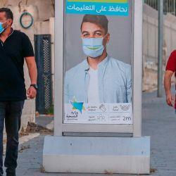 Hombres palestinos, con máscaras protectoras, pasan junto a una valla publicitaria de concientización sobre el coronavirus en el barrio de Beit Hanina en la Jerusalén oriental anexada por Israel. | Foto:AHMAD GHARABLI / AFP