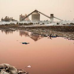 El humo se eleva frente a la fábrica de cemento SOCOCIM mientras los ahumadores de pescado artesanales trabajan a lo largo de la costa en Bargny. | Foto:JOHN WESSELS / AFP