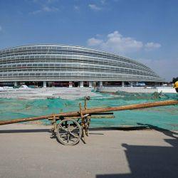 Un trabajador empuja una carretilla frente al Óvalo Nacional de Patinaje de Velocidad en construcción, el lugar para los eventos de patinaje de velocidad en los Juegos Olímpicos de Invierno de Beijing 2022, en Beijing. | Foto:WANG ZHAO / AFP