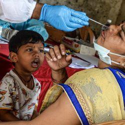 Un niño observa cómo un trabajador de salud recolecta un hisopo nasal de su madre durante una prueba de detección del coronavirus COVID-19 en Mumbai. | Foto:INDRANIL MUKHERJEE / AFP