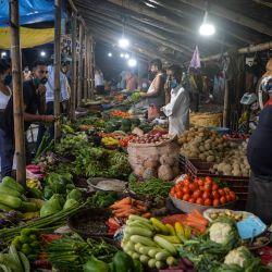 Los clientes compran verduras en Siliguri. | Foto:DIPTENDU DUTTA / AFP