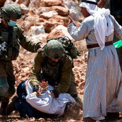 Soldados israelíes, enmascarados debido a la pandemia del coronavirus COVID-19, detienen a manifestantes palestinos y disparan botes de gas lacrimógeno cerca de la aldea de Shoufah, al sureste de Tulkarm en la ocupada Cisjordania, en medio de una protesta contra el despeje de tierras para expandir los asentamientos israelíes. | Foto:JAAFAR ASHTIYEH / AFP