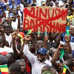 Un hombre sostiene una pancarta contra la Misión de Estabilización Integrada Multidimensional de las Naciones Unidas en Malí (MINUSMA) y Barkhane, una operación antiinsurgente que está dirigida por el ejército francés contra los grupos islamistas en la región africana del Sahel, durante una protesta para apoyar al ejército de Malí y al Comité Nacional para la Salvación del Pueblo (CNSP) en Bamako, Mali. | Foto:ANNIE RISEMBERG / AFP