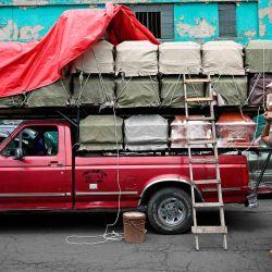 Los trabajadores descargan ataúdes de un camión frente a una funeraria ubicada frente al Hospital General en la Ciudad de México en medio de la pandemia del coronavirus COVID-19. | Foto:ALFREDO ESTRELLA / AFP