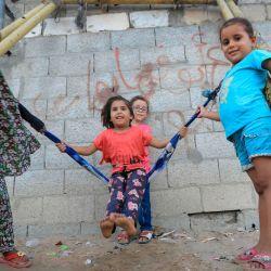 Niñas palestinas se balancean y juegan junto a su casa en Khan Yunis, en el sur de la Franja de Gaza. | Foto:MAHMUD HAMS / AFP