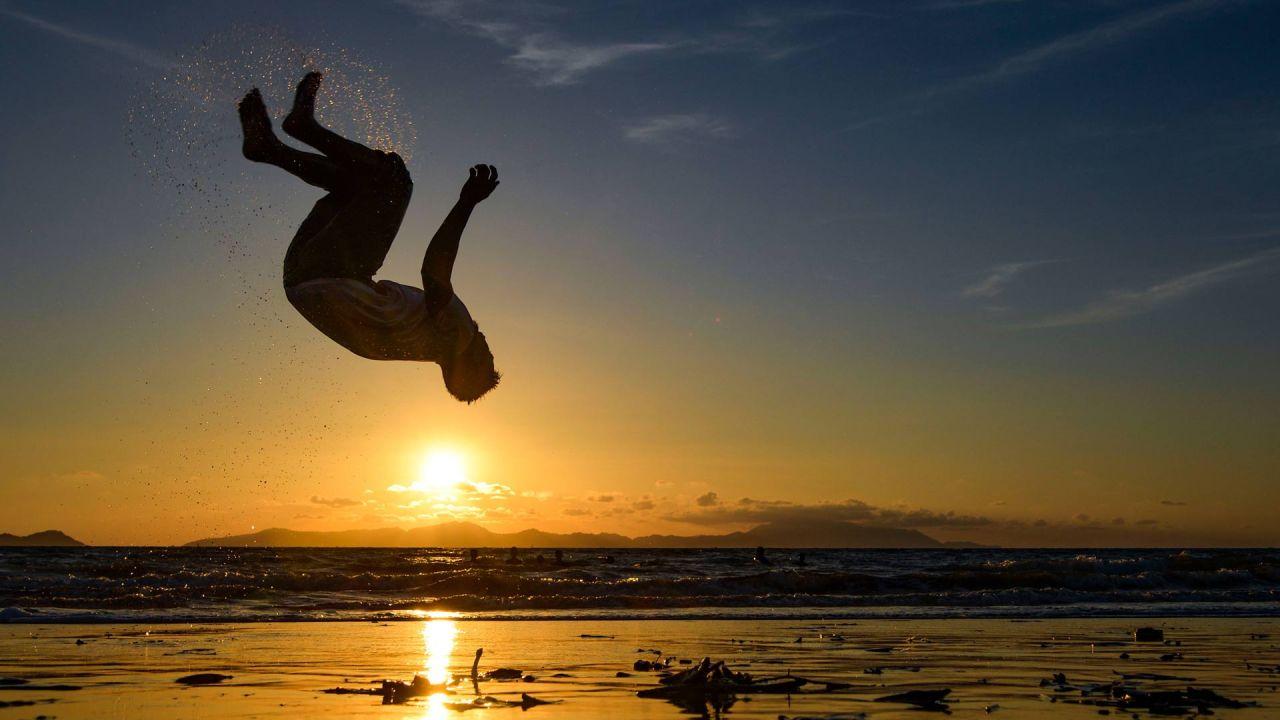Un hombre realiza un salto mortal en una playa al atardecer en Banda Aceh. | Foto:Chaideer Mahyuddin / AFP