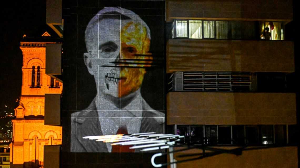 A man looks out a window as an image depicting Colombian former president Álvaro Uribe (2002-2010) is projected by the @lanuevabandadelaterraza (the new band of the terrace) on his building's wall, as part of a new way to protest in Medellin, Colombia, on August 9, 2020, amid the new coronavirus pandemic. As protests were silenced due to the lockdown imposed against the spread of the COVID-19, social and political demands started to be projected onto buildings in Latin America and lated shared through social networks.