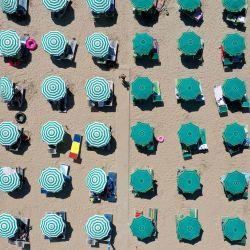 Una fotografía aérea muestra sombrillas en una playa del mar Adriático en Durres, mientras una ola de calor azota Europa. - Debido a la pandemia de Covid 19, la cantidad de turistas que ingresaron a Albania se redujo en un 66 por ciento. La mayoría de los turistas son nacionales o de los vecinos Kosovo y Macedonia del Norte. | Foto:GENT SHKULLAKU / AFP