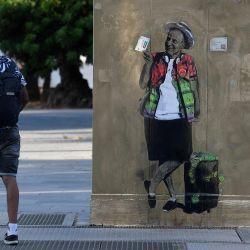 Un hombre pasa junto al arte callejero de TVBoy titulado  | Foto:Josep Lago / AFP