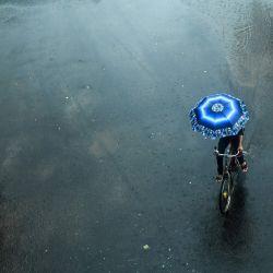 Un ciclista que lleva un paraguas recorre una carretera desierta bajo una intensa lluvia durante el primer día del bloqueo de dos días impuesto por el estado en Calcuta. | Foto:Dibyangshu Sarkar / AFP