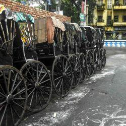 Los rickshaws tirados a mano están estacionados al costado de la carretera durante el segundo día del bloqueo impuesto por el estado de dos días como medida preventiva contra el aumento de casos de coronavirus COVID-19 en Calcuta. | Foto:Dibyangshu Sarkar / AFP