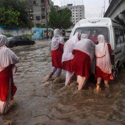 Los peatones empujan un vehículo a través de una calle inundada después de las fuertes lluvias monzónicas en la ciudad portuaria de Karachi en Pakistán. | Foto:Asif Hassan / AFP