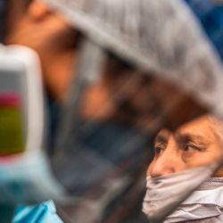 Un trabajador del Ministerio de Salud peruano examina y realiza una prueba para descartar COVID-19 en pacientes mayores de 60 años en sus casas de la colonia Perales, distrito de Santa Anita, al este de Lima. | Foto:Ernesto Benavides / AFP