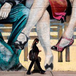 Una mujer camina frente a un mural relacionado con el tango en Buenos Aires.- Bailarines de todo el mundo competirán desde el miércoles en un mundo virtual de tango sin precedentes organizado por la Alcaldía de Buenos Aires cuando Argentina esté confinada en el peor momento de la pandemia, con más de 340.000 contagios y casi 7.000 muertes por COVID-19. | Foto:RONALDO SCHEMIDT / AFP