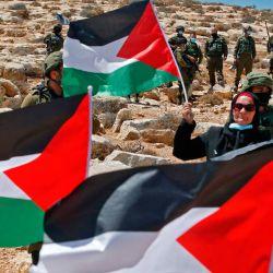 Los terratenientes y manifestantes palestinos levantan banderas nacionales mientras protestan por las actividades de construcción de asentamientos israelíes en sus tierras en la aldea de Al-Thaalaba, cerca de Yatta en el área (C), al sur de la ciudad de Hebrón en la Cisjordania ocupada. | Foto:HAZEM BADER / AFP