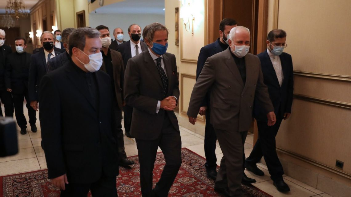 Director General of International Atomic Energy Agency, IAEA, Rafael Mariano Grossi, centre, is welcomed by Iran's Foreign Minister Mohammad Javad Zarif, centre right, for a meeting in Tehran, Iran, Tuesday, Aug. 25, 2020. Grossi arrived in Iran on Monday to press for access to sites where authorities are thought to have stored or used undeclared nuclear material. (AP Photo/Vahid Salemi)