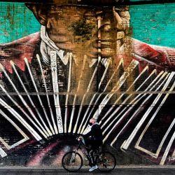Un hombre monta su bicicleta frente a un mural con la imagen de un músico de tango, en Buenos Aires.   Foto:RONALDO SCHEMIDT / AFP