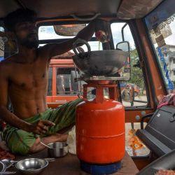 Un conductor de camión varado prepara comida dentro de un camión estacionado durante el segundo día del bloqueo impuesto por el estado de dos días como medida preventiva contra el aumento de casos de coronavirus COVID-19 en Siliguri.   Foto:DIPTENDU DUTTA / AFP