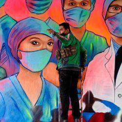 El artista urbano mexicano Sergio Morelos, alias Applezman, pinta un mural en homenaje a los médicos y enfermeras que están en la primera línea de la lucha contra el nuevo coronavirus COVID-19, en la Ciudad de México.   Foto:Alfredo Estrella / AFP