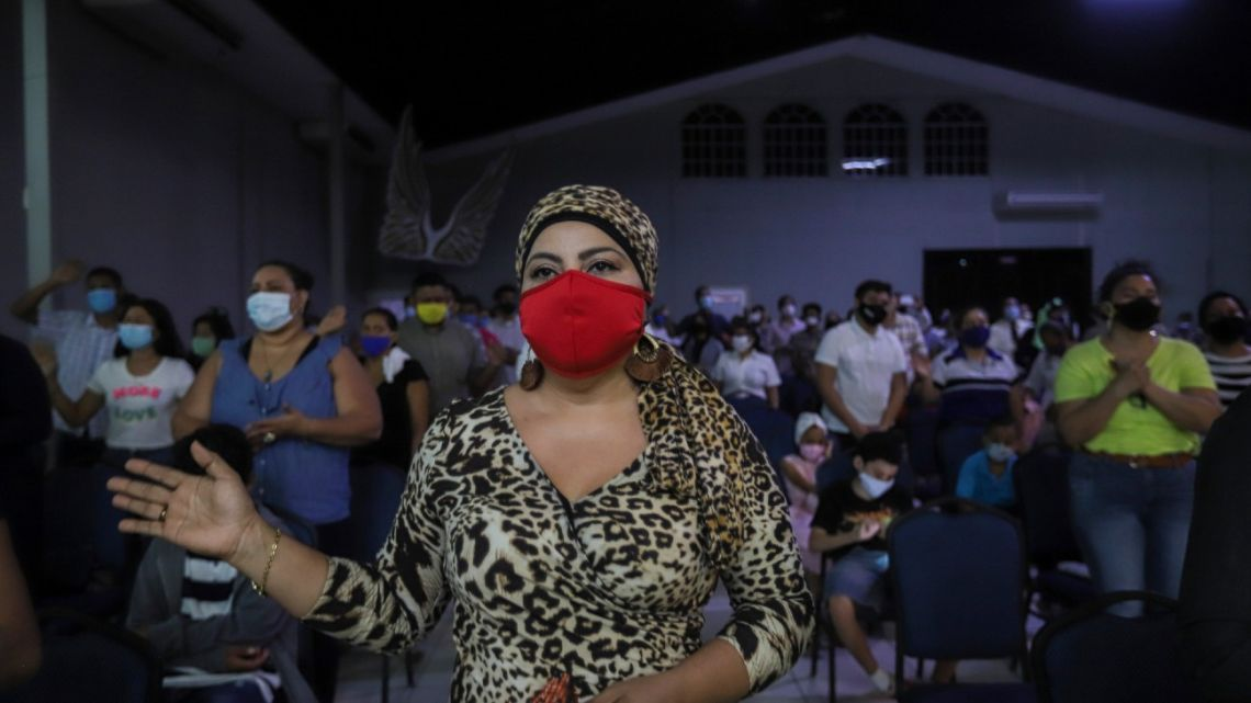 Women wearing masks to curb the spread of the new coronavirus pray during the afternoon service at Bethel evangelical church in Managua, Nicaragua, Wednesday, Aug. 12, 2020. The congregation knows the pandemic's wrath: two of its pastors were among the more than 40 evangelical leaders who have died in Nicaragua since March.