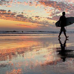 Un surfista sale del agua al atardecer en Los Ángeles.   Foto:Chris Delmas / AFP