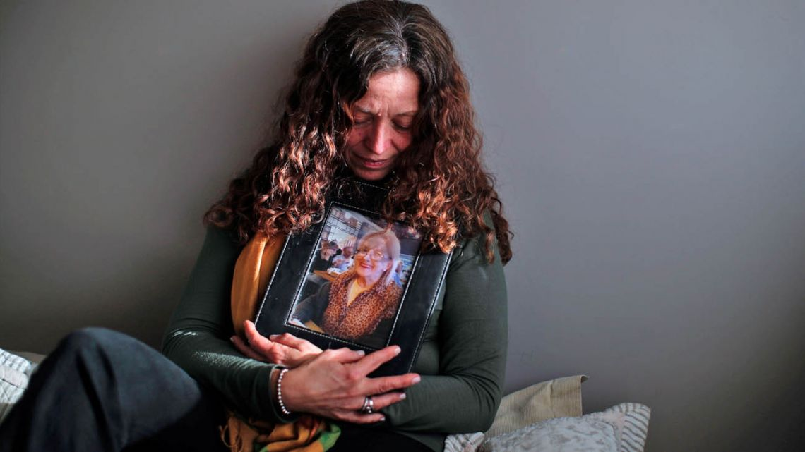 Fernanda Mariotti cradles a picture of her mother Martha Pedrotti, who passed away a victim of COVID-19, at her home in Buenos Aires.