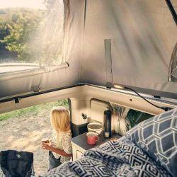 La cama superior tiene ventanas laterales con mosquiteras integradas y luces LED de lectura.