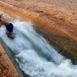 Los palestinos se deslizan en un canal de agua utilizado para el riego para refrescarse mientras las temperaturas suben en la ciudad de Jericó en Cisjordania a 44 grados Celsius. | Foto:AHMAD GHARABLI / AFP