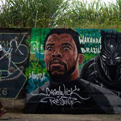 Un transeúnte observa una pintura mural en honor al fallecido actor estadounidense Chadwick Boseman, en el barrio de Lapa en Río de Janeiro, en medio de la pandemia de coronavirus. - Boseman, protagonista de la innovadora película de superhéroes  | Foto:MAURO PIMENTEL / AFP