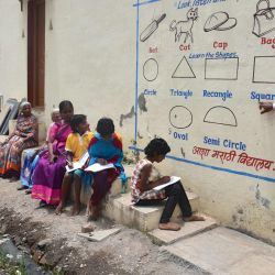 Un maestro de escuela de Aasha Marathi Vidyalay, señala un escrito de libros de texto de varios temas pintados en la pared de una casa para enseñar a los estudiantes que no pueden llevar teléfonos inteligentes a asistir a clases escolares en línea. en medio de la pandemia del coronavirus Covid-19 en Solapur, en el estado de Maharashtra. | Foto:AFP