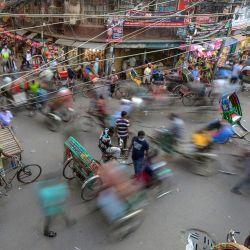 Los tiradores de rickshaw se abren paso entre los peatones en una calle muy transitada en el mercado mayorista Chawk Bazar en Dhaka. | Foto:Munir Uz zaman / AFP