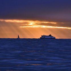 Un yate y un ferry transcanal se ven en el Canal al amanecer, frente a la costa sureste de Inglaterra. | Foto:GLYN KIRK / AFP