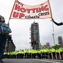 Los activistas sostienen una pancarta que dice  | Foto:JUSTIN TALLIS / AFP