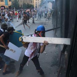 Los manifestantes libaneses intentan asaltar una puerta durante una manifestación contra el gobierno en el centro de la capital del Líbano, Beirut. | Foto:AFP