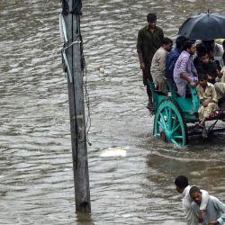 Los hombres montan un carro tirado por caballos en una calle inundada durante las fuertes lluvias monzónicas en Lahore. | Foto:Arif Ali / AFP