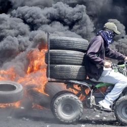 Un manifestante palestino entrega neumáticos durante los enfrentamientos con las fuerzas de seguridad israelíes tras una manifestación para protestar contra el plan de Israel de anexar partes de la ocupada Cisjordania, en la aldea de Kfar Qaddum. | Foto:JAAFAR ASHTIYEH / AFP