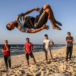 Un joven realiza una voltereta mientras otros miran a lo largo de una playa a orillas del mar Mediterráneo en Rafah, en el sur de la Franja de Gaza. | Foto:SAID KHATIB / AFP