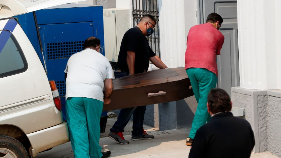 Forensic workers carry a coffin, containing the remains of an 11-year-old Argentine girl killed in a police and military operation against a rebel group, at a morgue in Asunción, Paraguay, on Saturday, September 5, 2020.